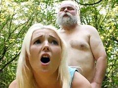 Joven rubia linda tiene relaciones sexuales con un anciano en el bosque